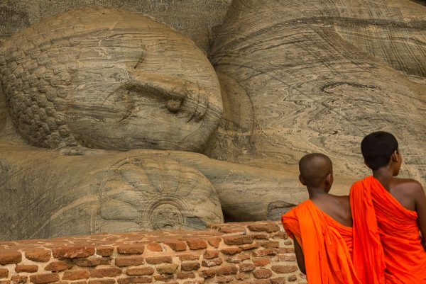 2 novice monks next to a resting buddha part of a sri lanka photo essay