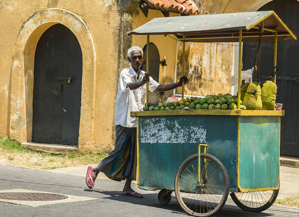 elderly man pushing a cart of fruit for sale