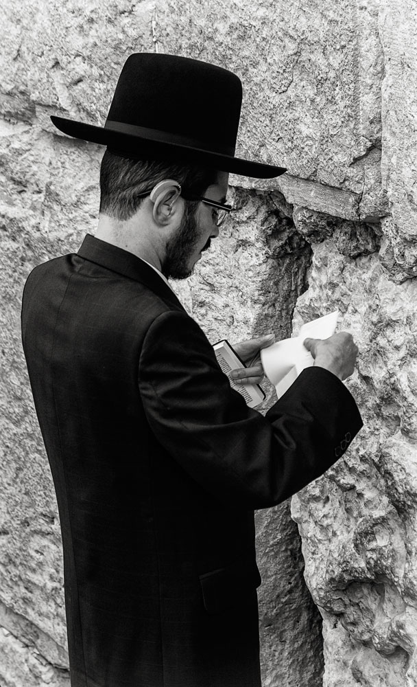 orthodox jewish man reading a prayer in front of jerusalem's western wall