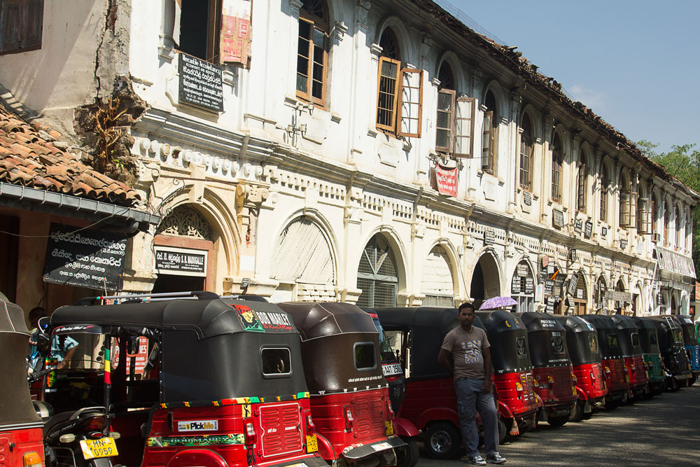driver posing next to a line of auto rickshaws against colonial buildings in sri lanka