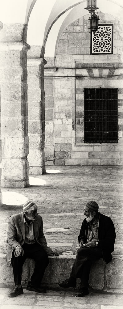 2 muslim men sitting on step and talking on temple mount jerusalem