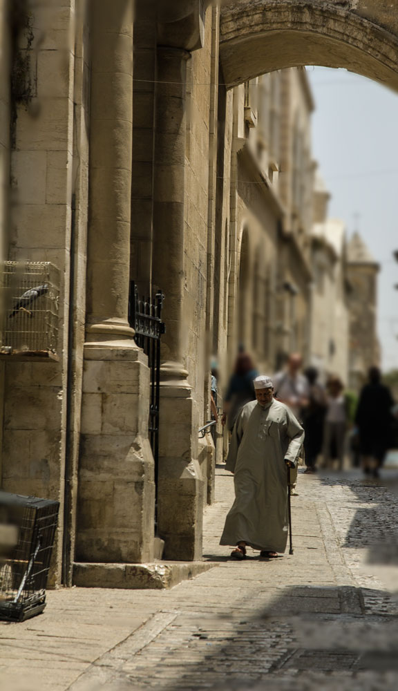 man walking through arch in street in old city of jerusalem