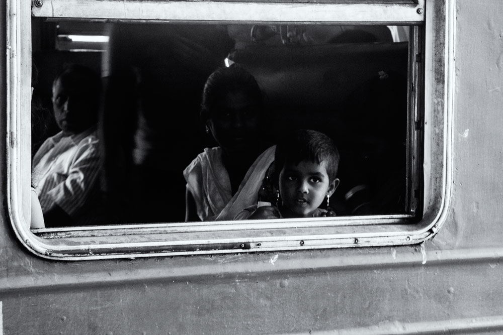 mother and child peering out of train window in sri lanka