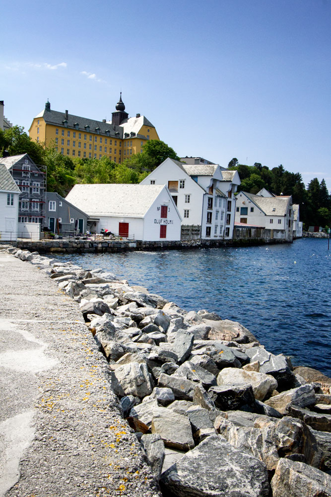 stone pier leading to wooden houses in alesund norway