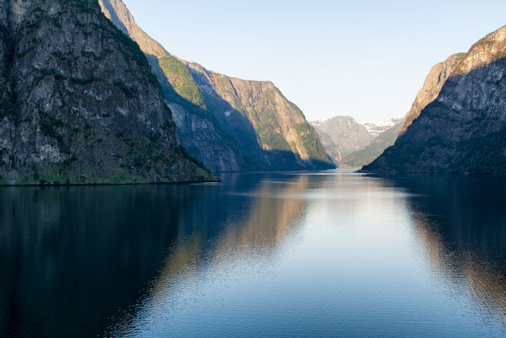 fjord in norway with mountains reflected in still water