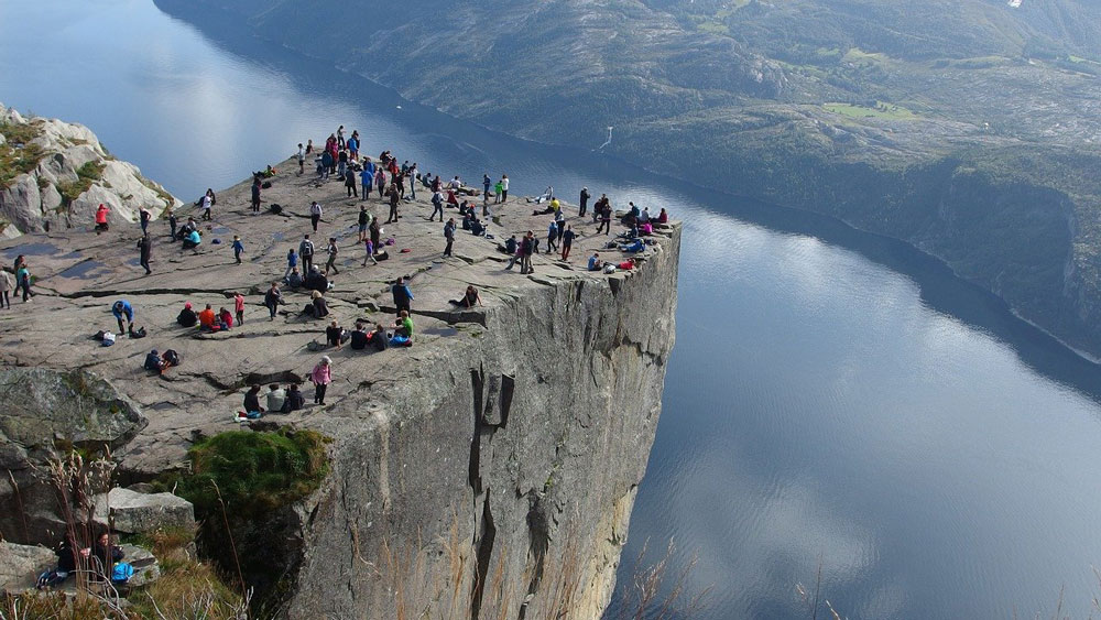 group of people on pulpit rock a table like plateau jutting over a fjord