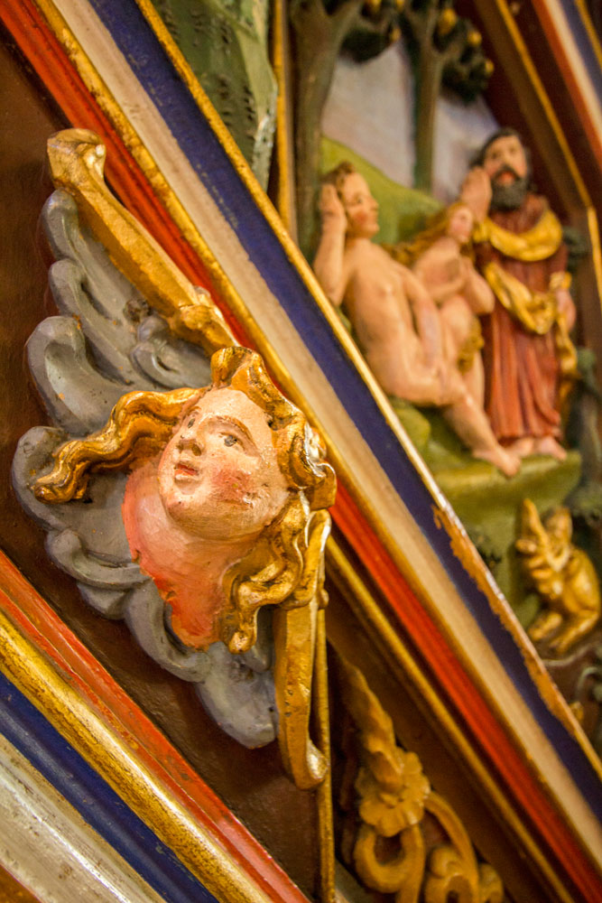 brightly colored wooden cherubs inside cathedral in stavanger