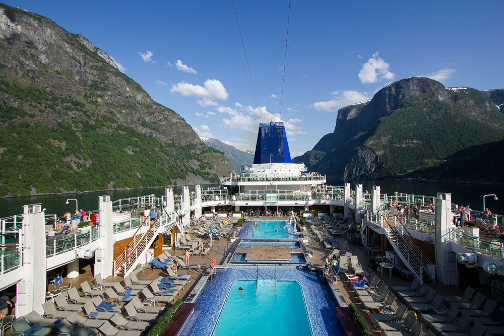 deck of cruise ship sailing along narrow norway fjords with hills on either side