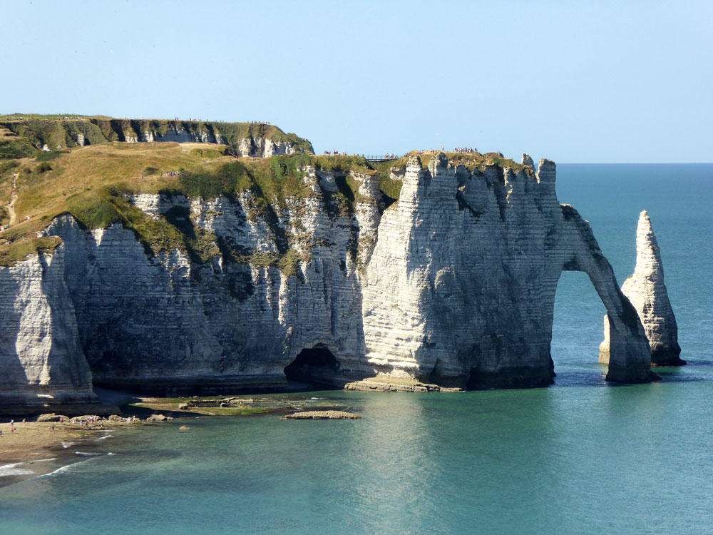 cliffs hewn into a stone arch over ocean in etretat normandy
