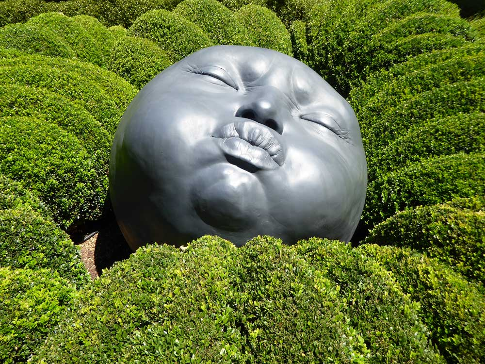 Sculpture of face amongst greenery at Jardins d'Etretat