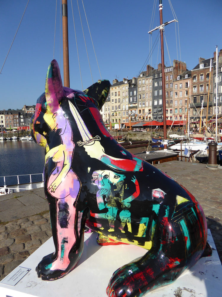 statue of huge painted cat overlooking harbout with boats and houses in honfleur normandy