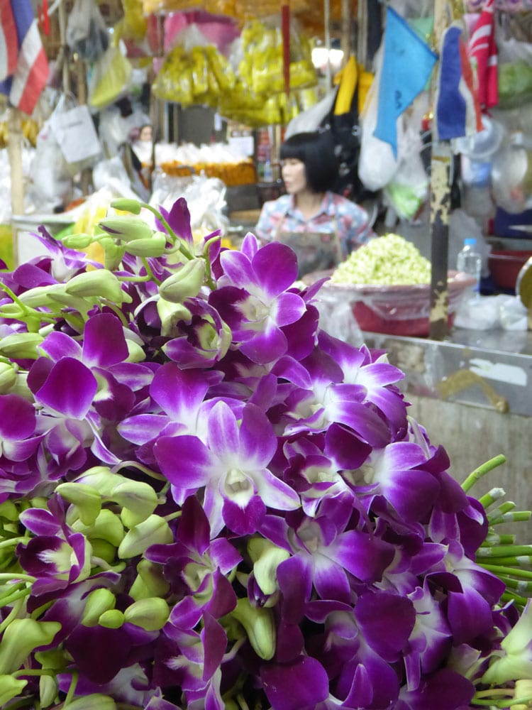 flowers on sale in bangkok flower market with woman in background