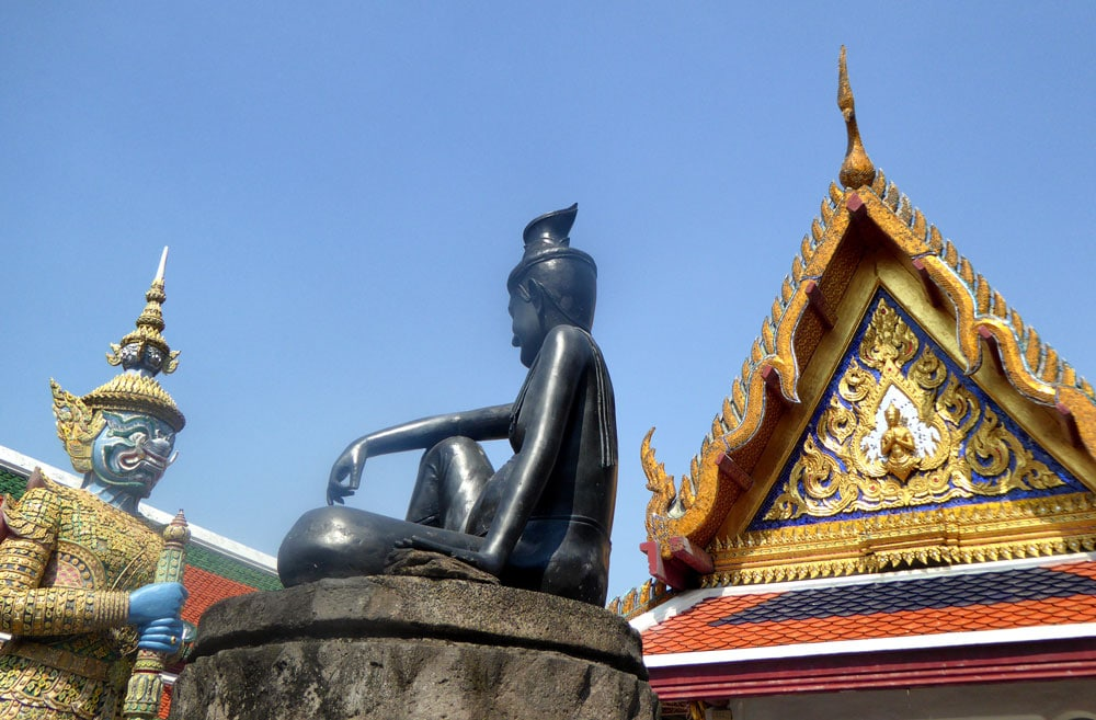 two statues and a brightly coloured pagoda in diy bangkok temple tour