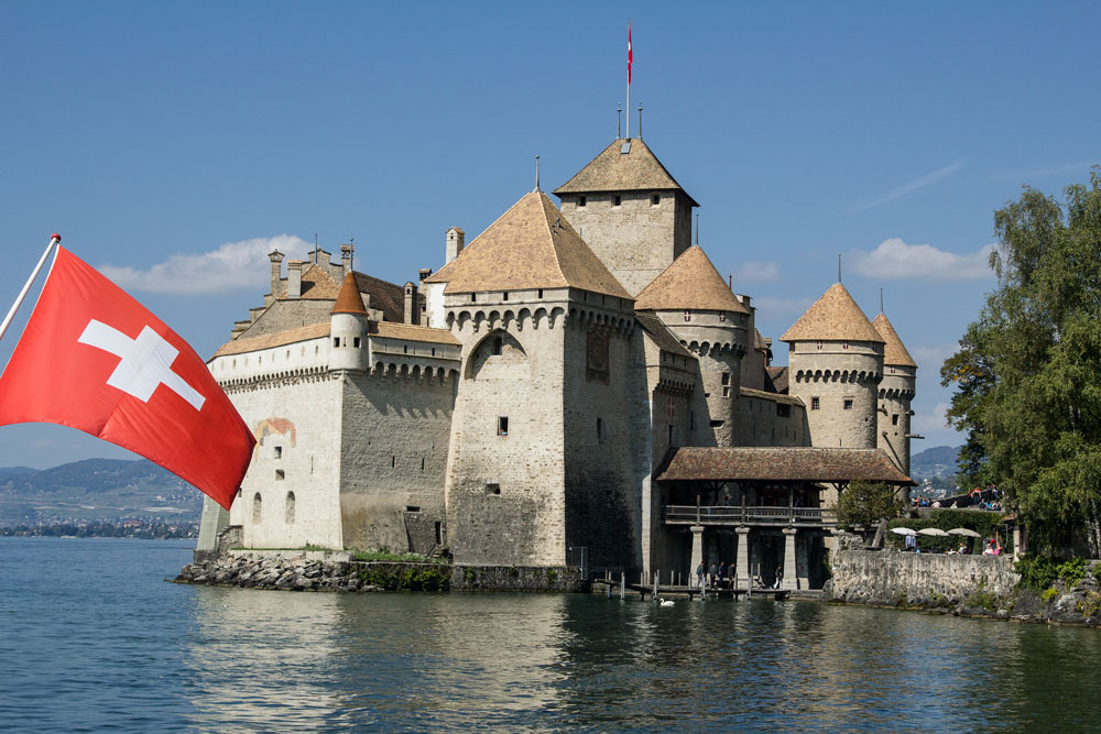 castle on lake with swiss flag in foreground