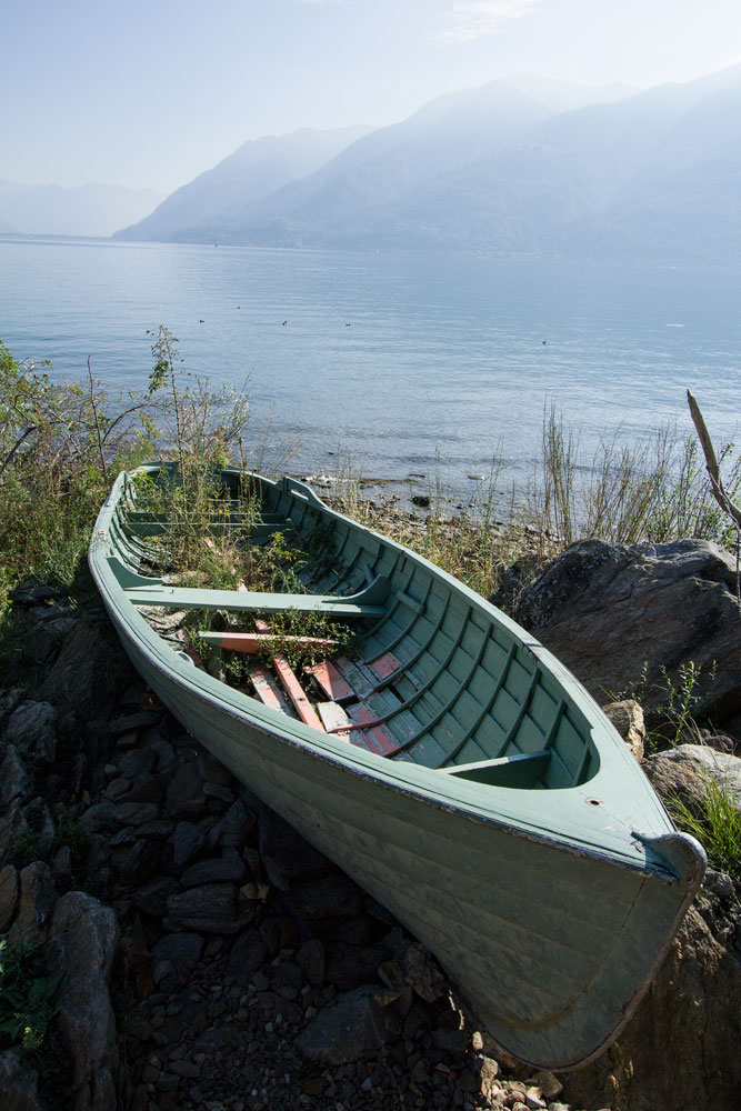 green wooden rowing boat by lakeside