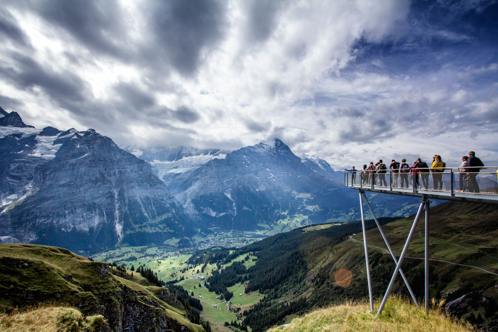 group of people on elevated walkway overlooking dramatic alpine scenery