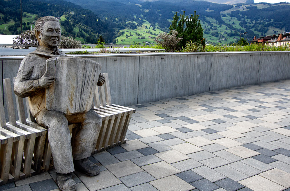 sculpture of man playing an accordion on a bench