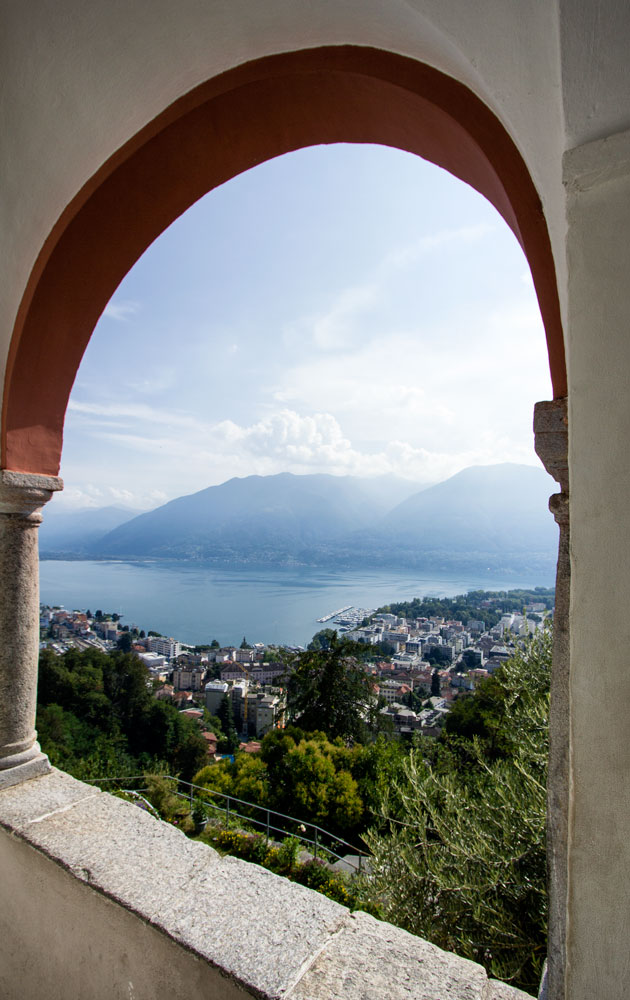 view of lake and mountains through the arched window of a church loggia