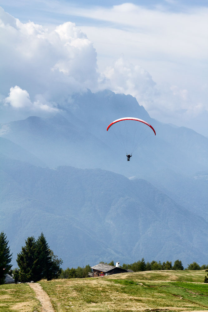 person paprgliding over swiss mountain