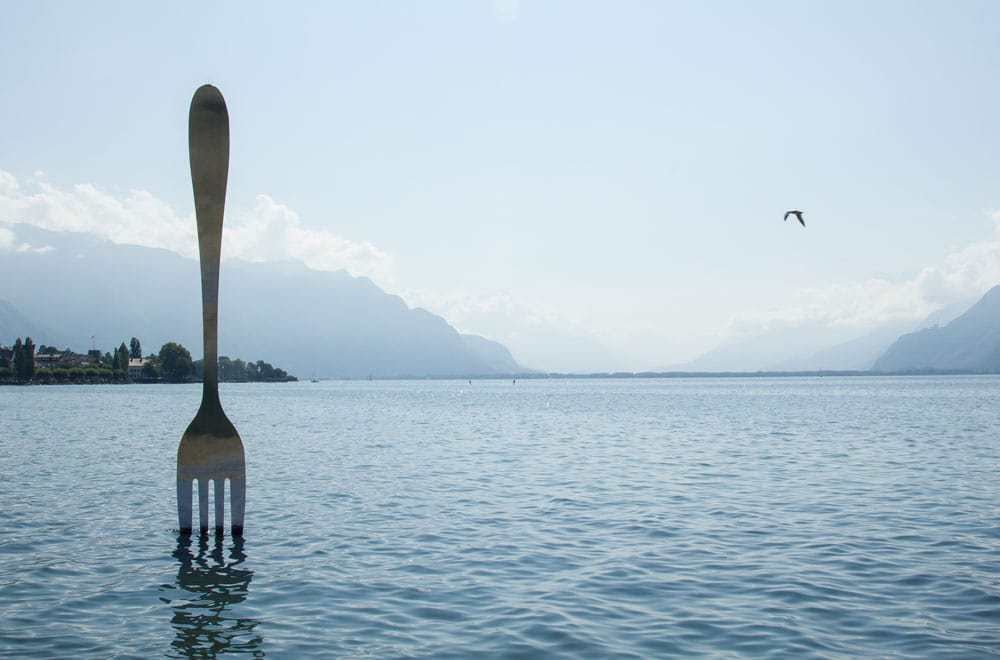 sculpture of fork sticking out of lake
