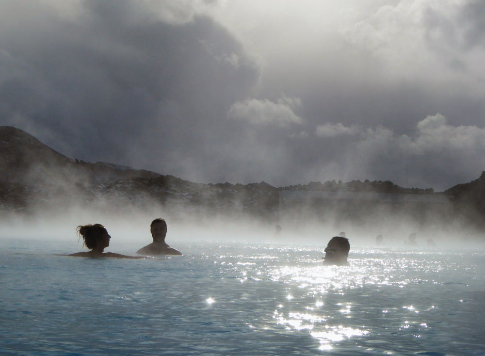 people bathing in blue lagoon iceland with steam mist