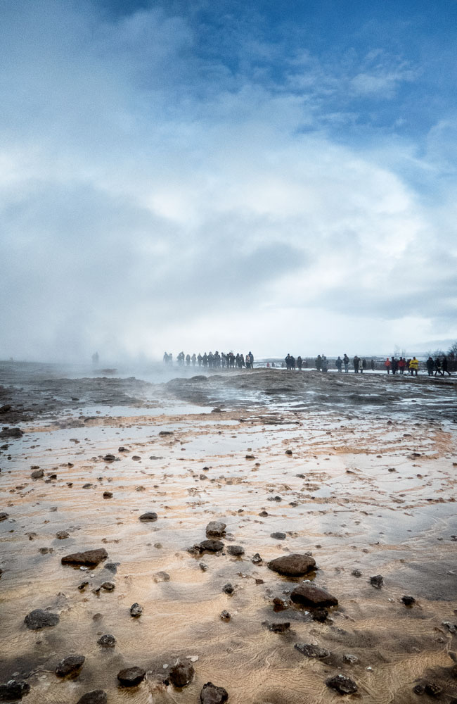 people walking through steaming lava field in geysir iceland