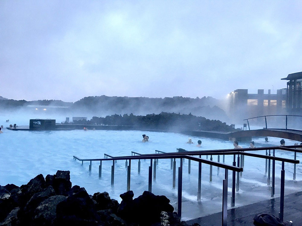 people bathing in blue water of blue lagoon iceland