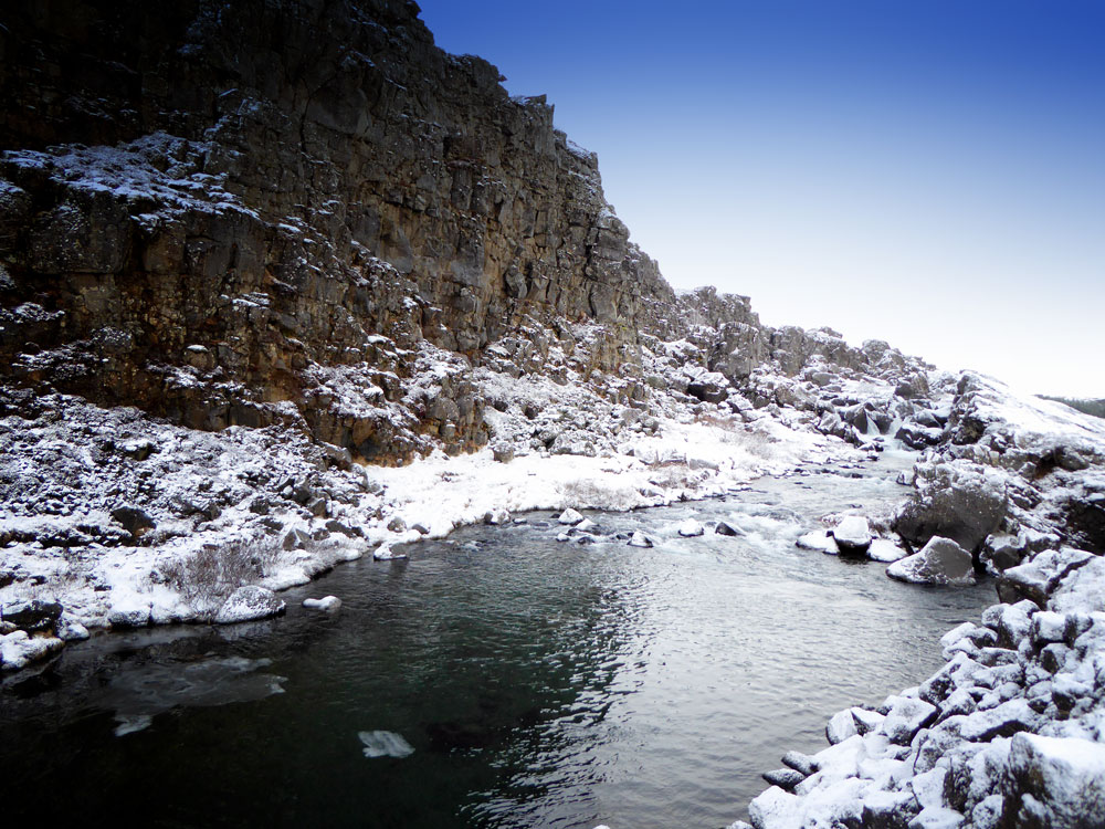 glacial stream running through snow covered basalt rock at Thingvellir one if the Iceland Golden Circle stops