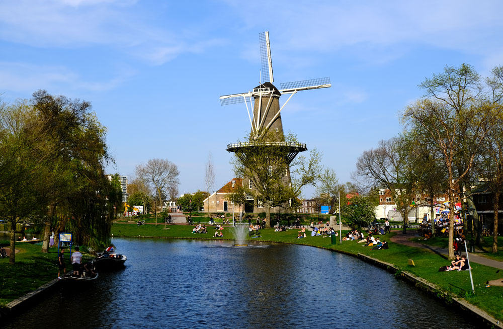 windmill at the side of canal with people sitting on canal bank