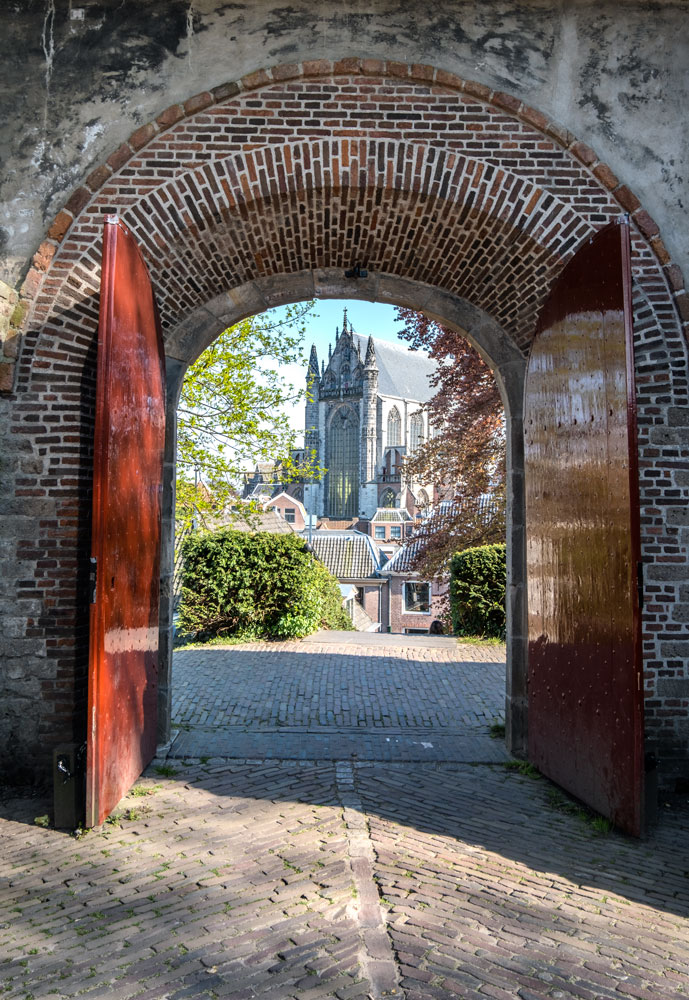 church seen through arched gateway in leiden