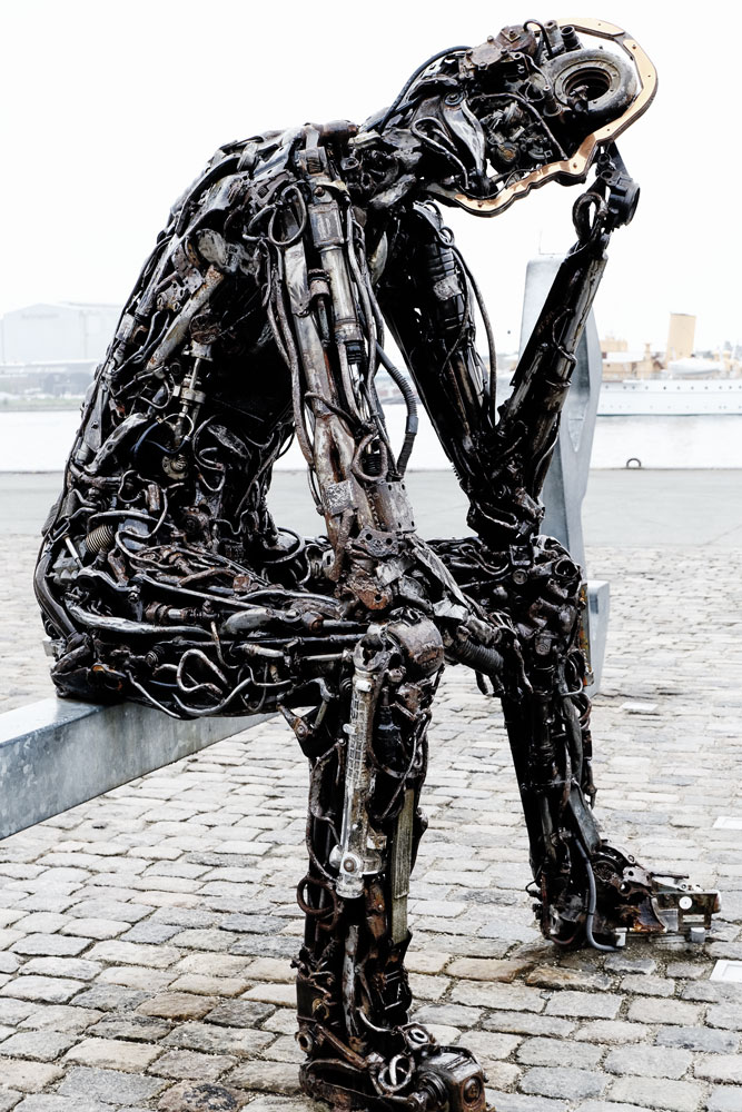 sculpture of thinking man made out of car parts