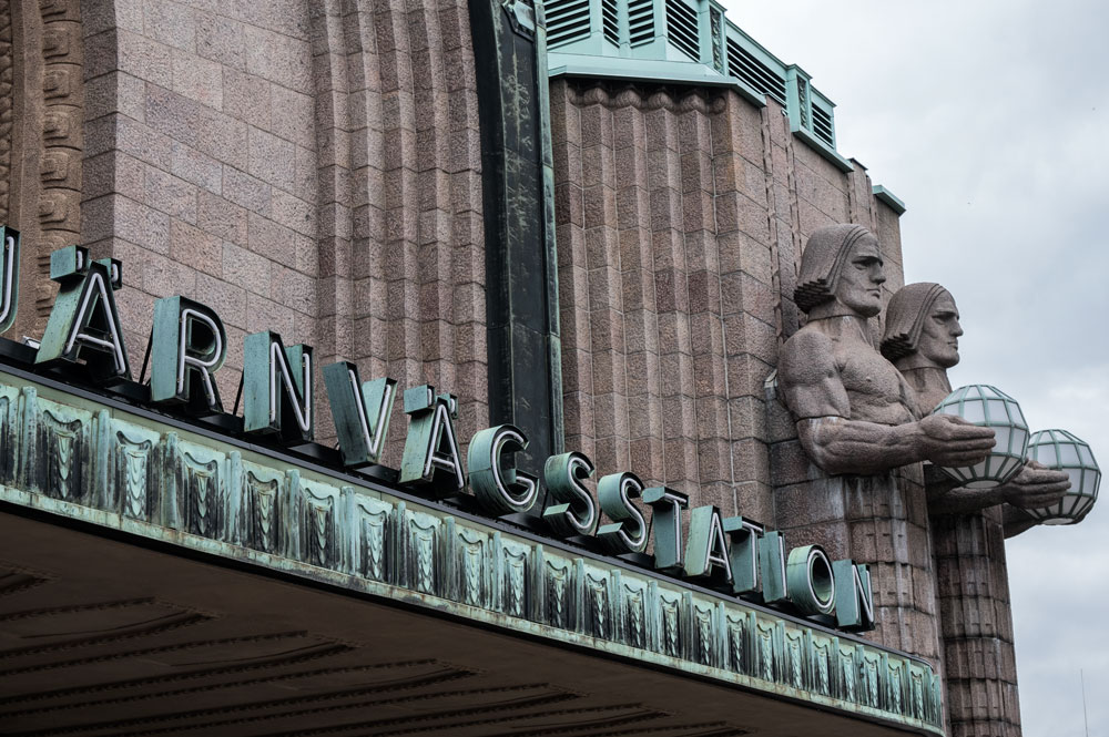 art deco sculptures of men and sign for helsinki railway station