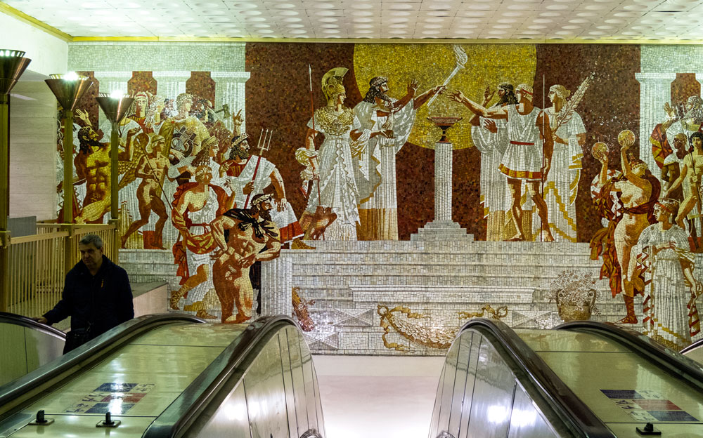 man in escalator in Sportivnaya station, St. Petersburg with background mosaic