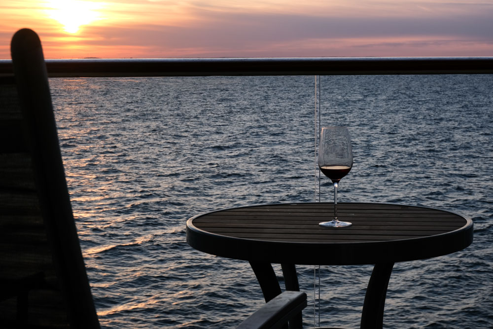 glass of red wine on table of cruise ship balcony cabin