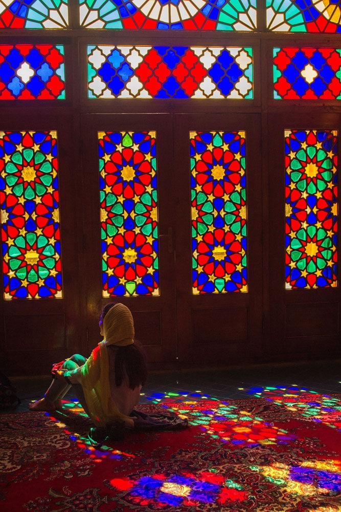 woman sitting on carpet in mosque bathed in multicolored light