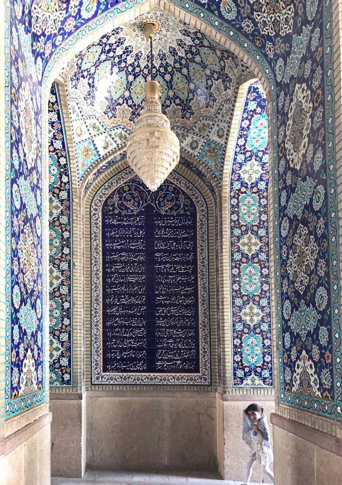girl running through mosque with blue and white tiles