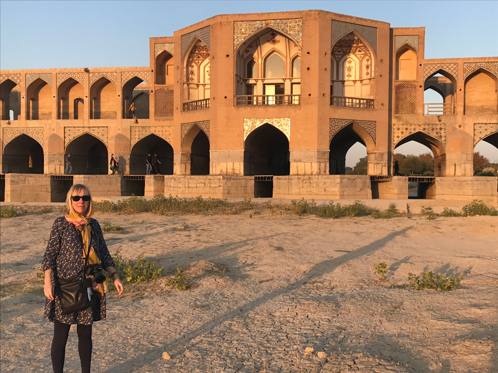 woman posing in front of sandstone bridge in iran