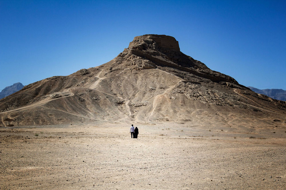two people in desert in iran in front of a large mound