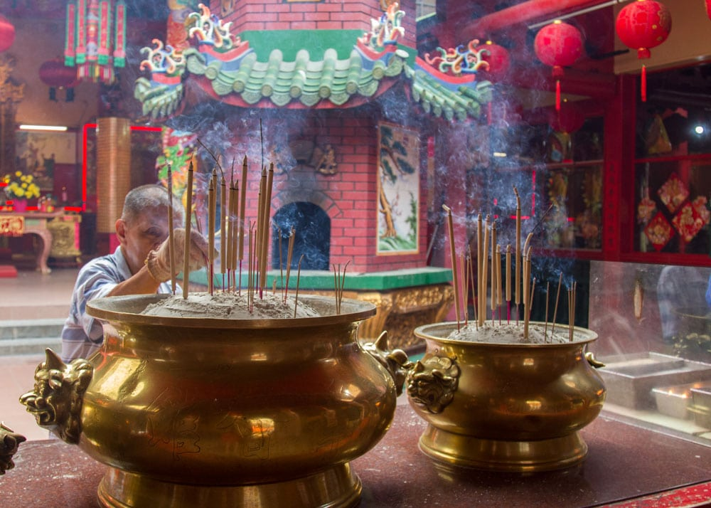 old woman lighting incense stick in chinese temple