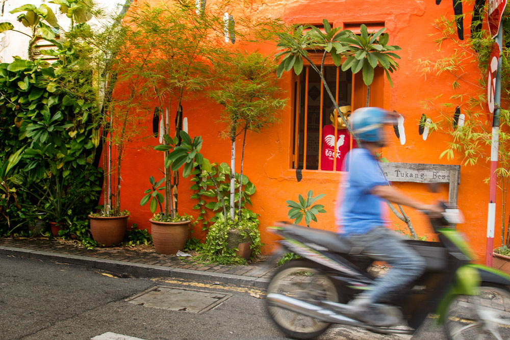 man on scooter riding past bright orange building in melaka malaysia