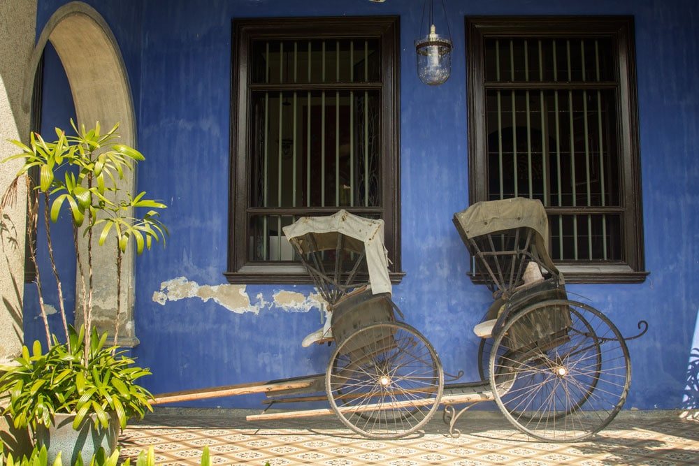 cycle rickshaw in front of bright blue building in penang malaysia