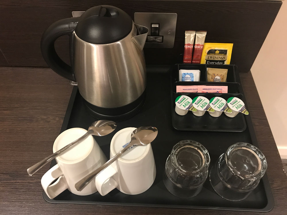 tray with kettle and cups and tea and coffee supplies