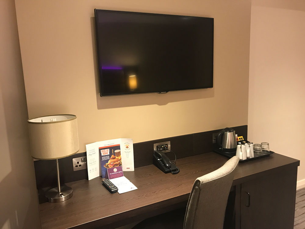 chair and desk with tv on wall in premierr inn london heathrow terminal 4 room