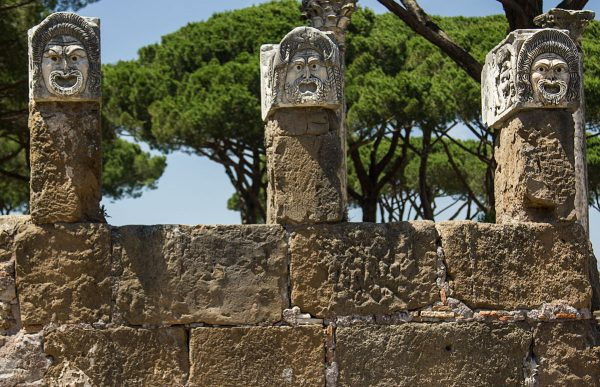 stone heads on top of columns at the ancient roman site of ostia antica vivited as a day trip from rome