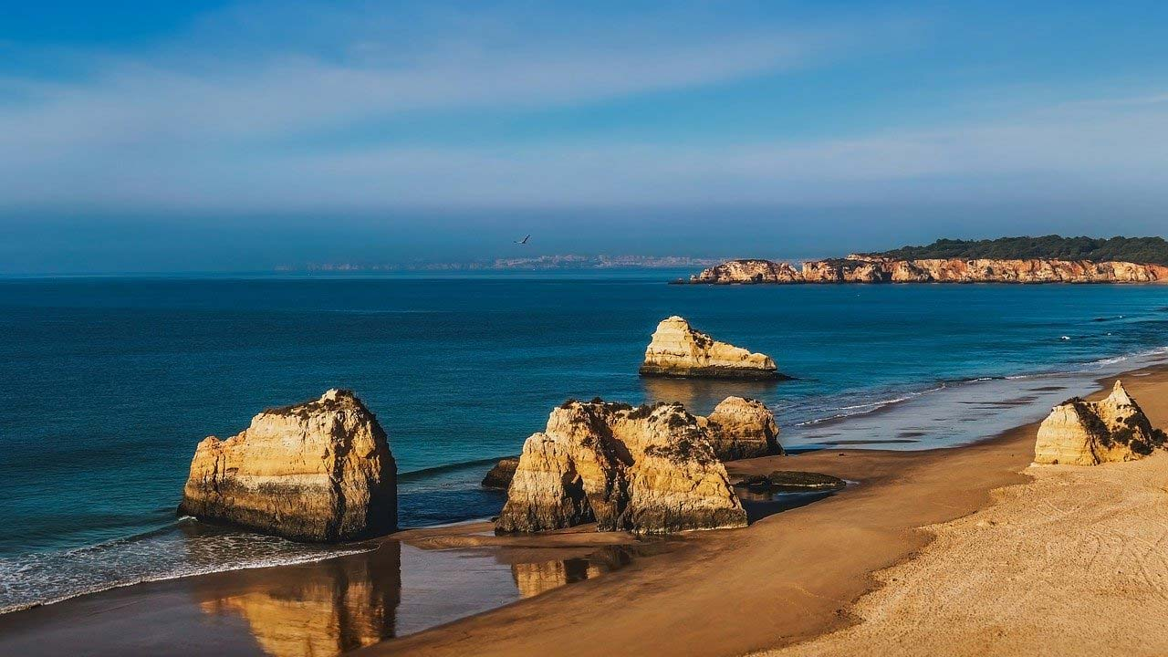 coast of algarve portugal with deep blue sea and rocks and beach