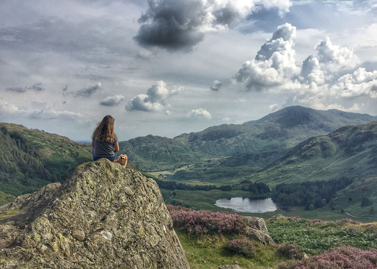 woman-with-dog-overlloking-hills-and-lake-of-lake-district-england