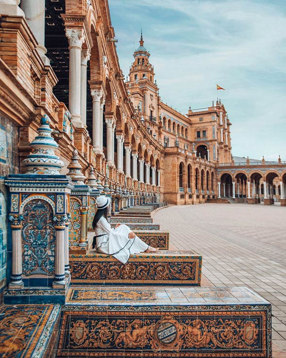 woman-wearing-hat-sitting-on-tiled-steps-in-square-in-Seville