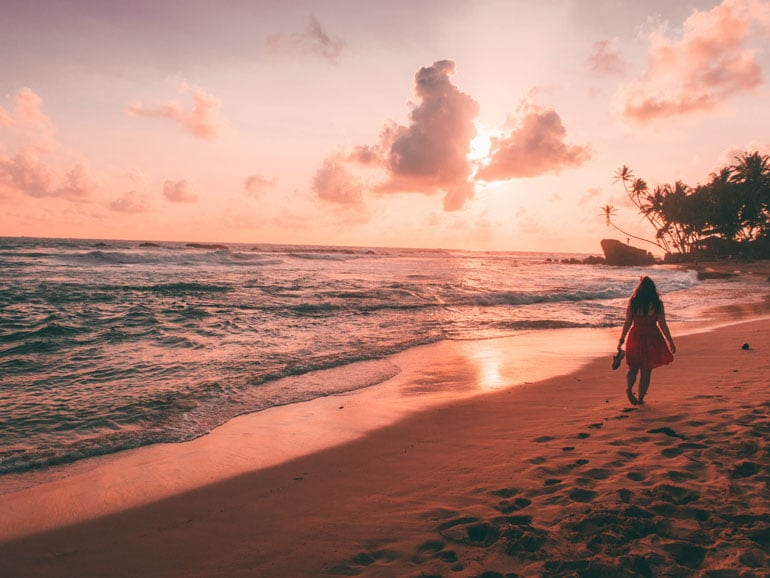 woman-walking-along-Unawatuna-beach-at-sunset