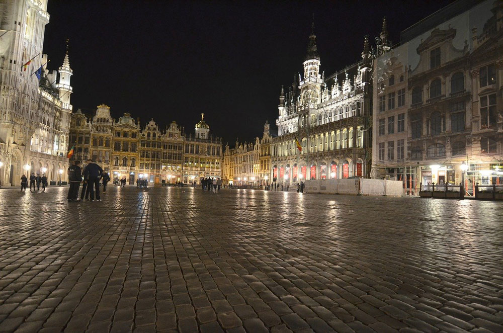 flemish buildings lining cobblestone square in brussels at night