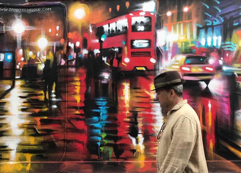 street art of man walking past london street in the rain at night